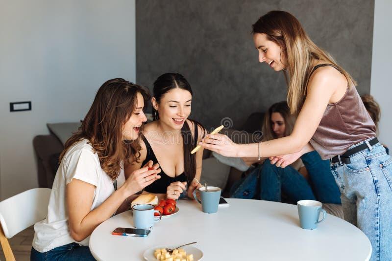 Frukost för tre kvinnavänner i köket royaltyfri fotografi
