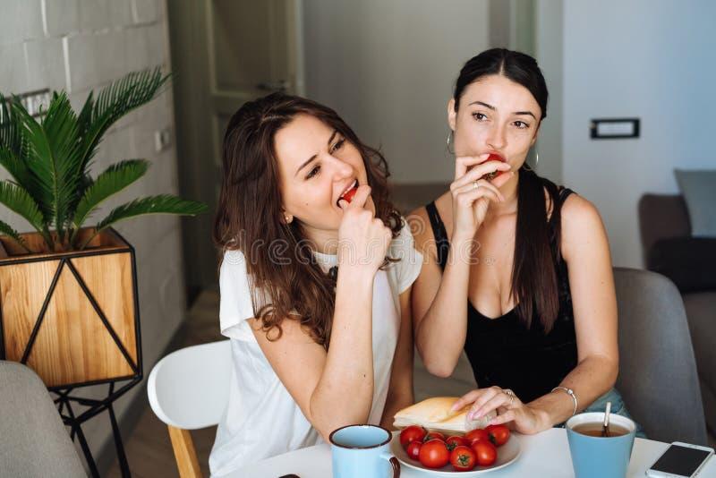 Frukost för två kvinnavänner i köket arkivfoton