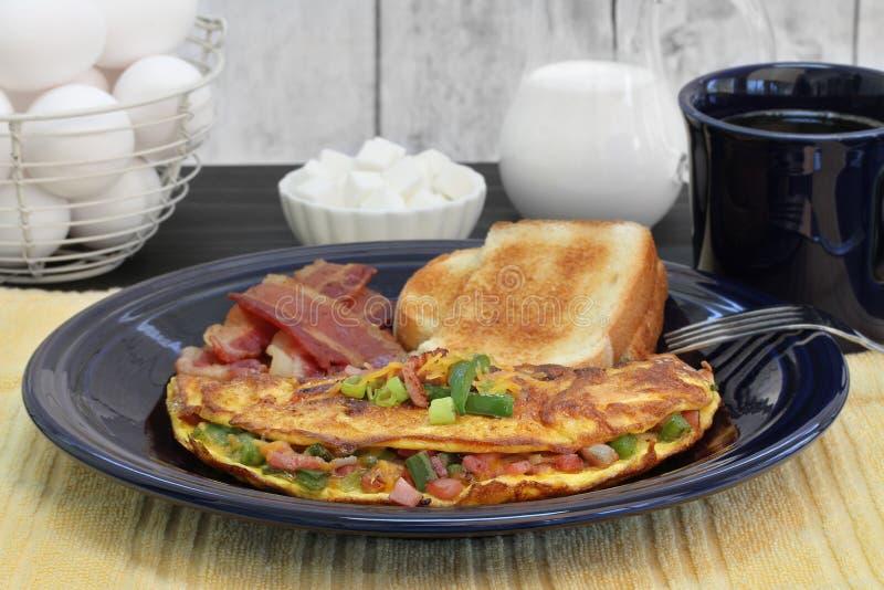 Frukost för västra omelett med rostat bröd och bacon Selektivt fokusera royaltyfria bilder
