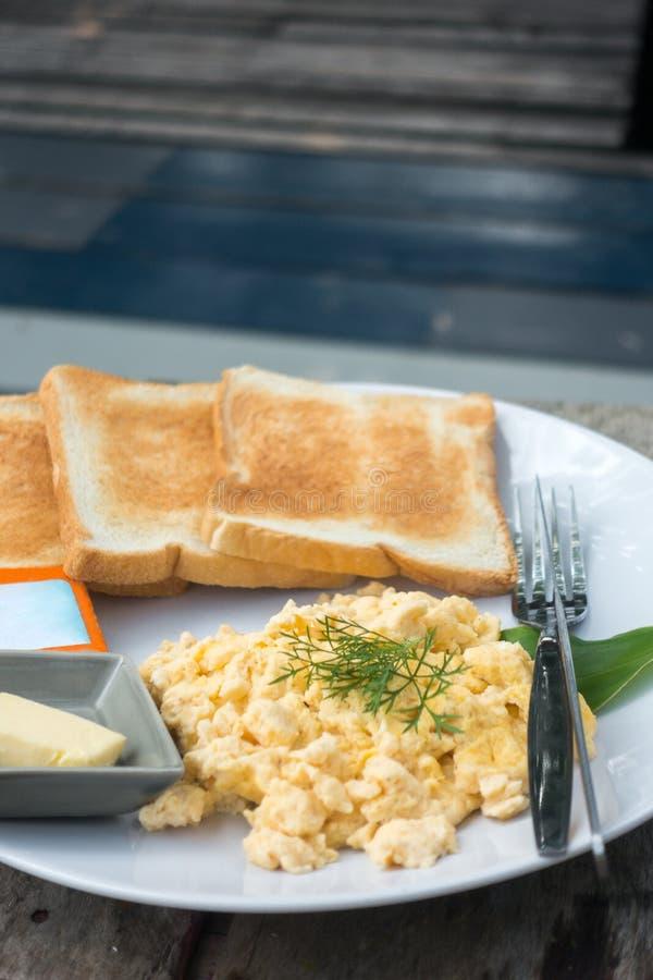 frukost & x28; Förvanskad ägg och bread& x29; med wood bakgrund arkivfoton