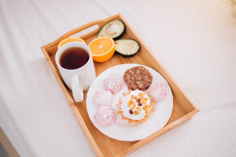 Frukost f?r bra morgon i s?ng med te, apelsin, avokado, kaka, marshmallower, chokladkex i tr?magasin livsstil mat, arkivfoto