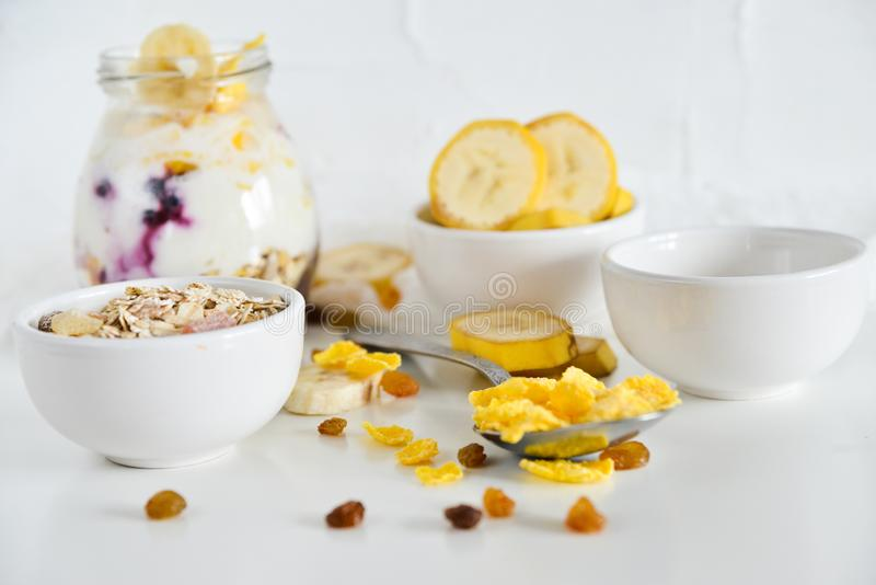 Frukost i en krus: sädesslag banan, nya bär, granola, yoghurt på en ljus bakgrund Begreppet av sunt äta, hög-carb arkivfoto