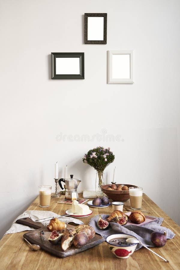 Frukost i kök med fotoramar på den vita väggen Giffel fikonträd, kaffe, bröd på trätabellbakgrund, utrymme för orientering royaltyfri fotografi