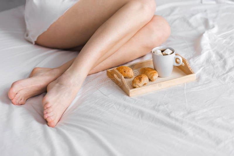 Frukost i säng med koppen av svart kaffe och giffel för kvinna royaltyfri foto