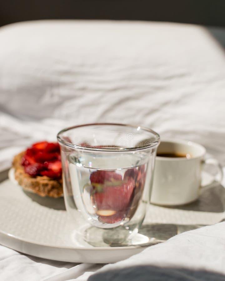 Frukost i säng med morgonsolljus Elegant magasin med rostat bröd och nytt jordgubbar, kaffe och morgonexponeringsglas av vatten s royaltyfri foto