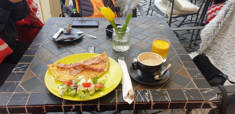 Frukost i Timisoara Rumänien den fackliga fyrkanten med kaffe och omellete och orange fruktsaft och sallad royaltyfri fotografi