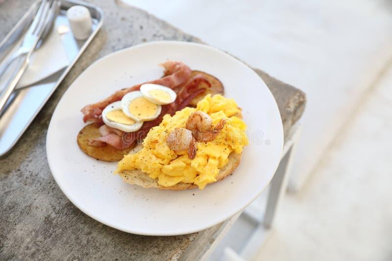 Frukost med förvanskade ägg, stekte potatisar bacon och räka royaltyfria bilder