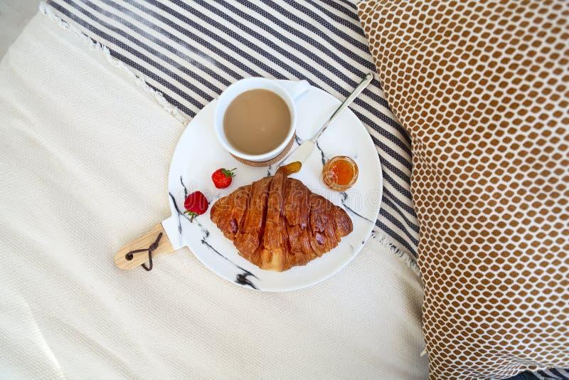 Frukost med gifflet, kaffe, jordgubben och driftstopp på plattamagasinet i säng royaltyfri foto