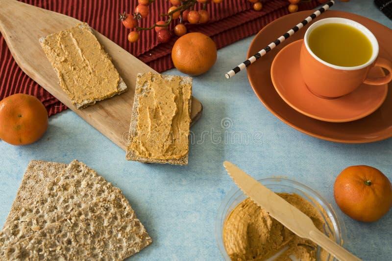 Frukost med hummus på rostat bröd, med mandariner och orange fruktsaft royaltyfria bilder