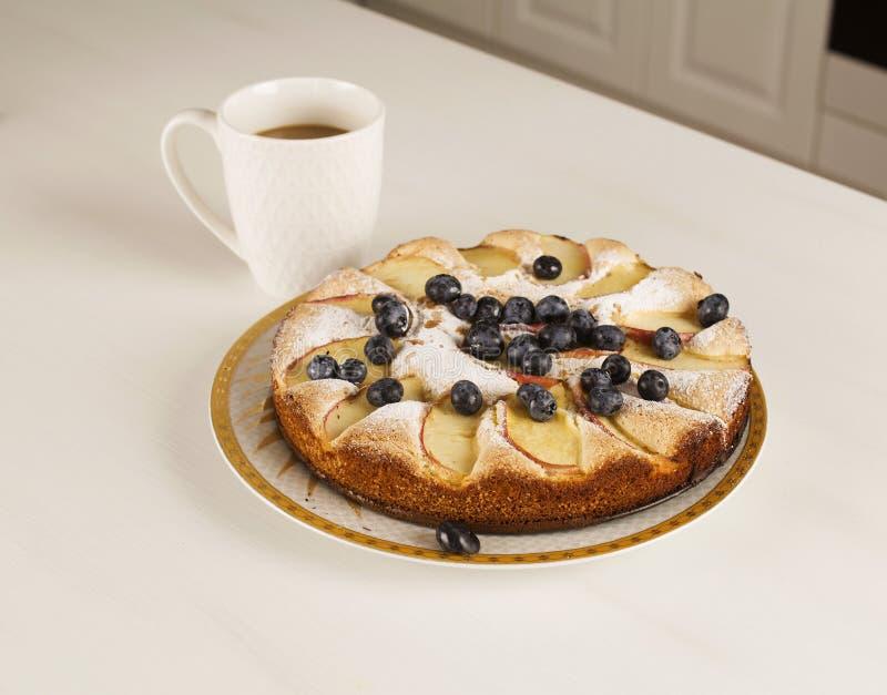 Frukost med kaffe och stor smakrik paj på bordet arkivbild