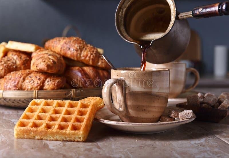 Frukost med svart kaffe och nya bakelser arkivfoton