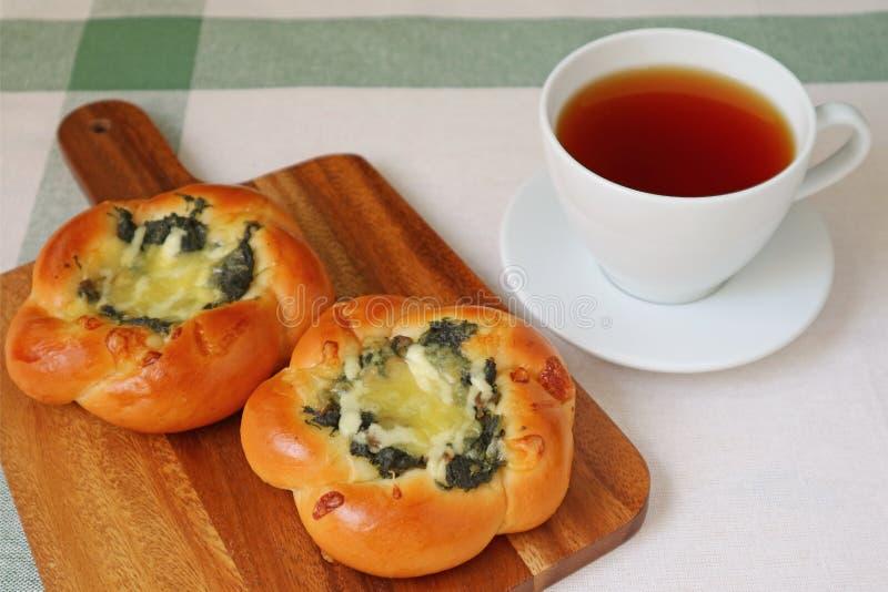 Frukost med varma te- och spenat- och ostbullar royaltyfri bild