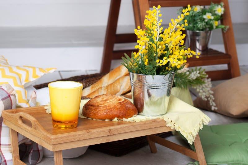 Frukost på den hemtrevliga verandan Hemlagad lemonad på farstubron på en varm dag Sommarlandsgård med kuddar, mimosablommor och l arkivbild