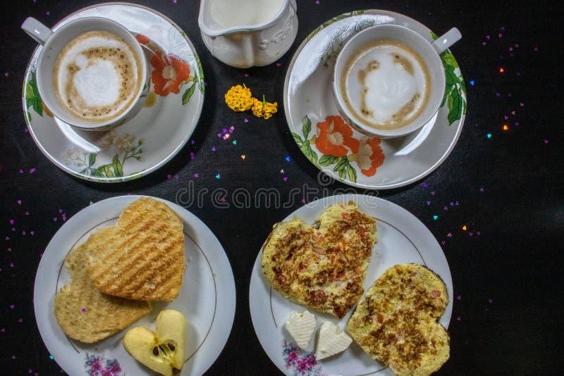 Frukost på valentin dag - stekt omelete, bröd, äpple och vit ost i formen av en hjärtacoffe och att mjölka Top beskådar royaltyfri bild