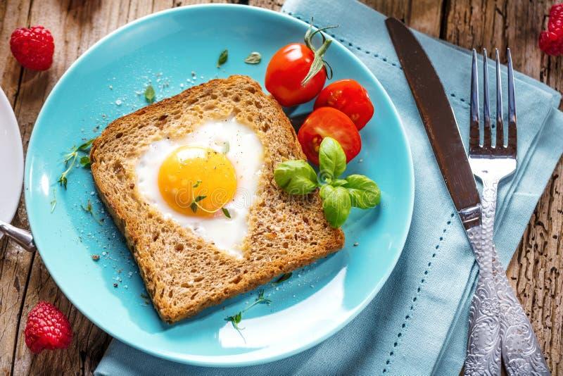 Frukost på valentin dag - stekte ägg och bröd i formen av en hjärta och nya grönsaker royaltyfri bild