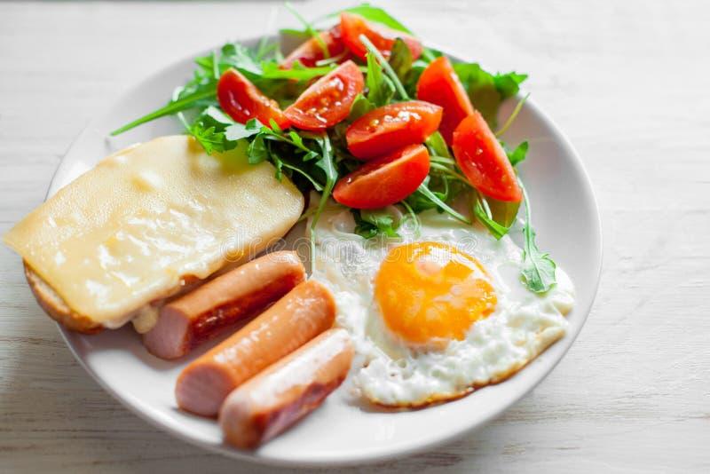 Frukost som inkluderar ägg, korvar, sallad och rostat bröd arkivfoto