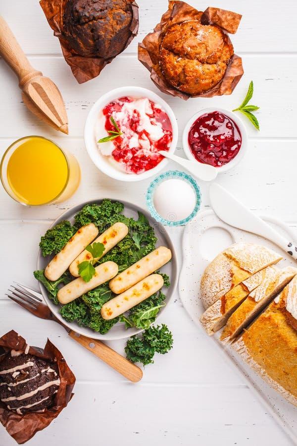 Frukost som tjänas som med muffin, grillade korvar, fruktsaft, ny br royaltyfria foton