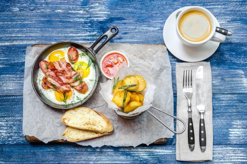 Frukost: stekpanna med ägg och kött, potatisar, sås, kaffe och bestick, på en blå grov bomullstvillbakgrund ovanför sikt royaltyfri foto