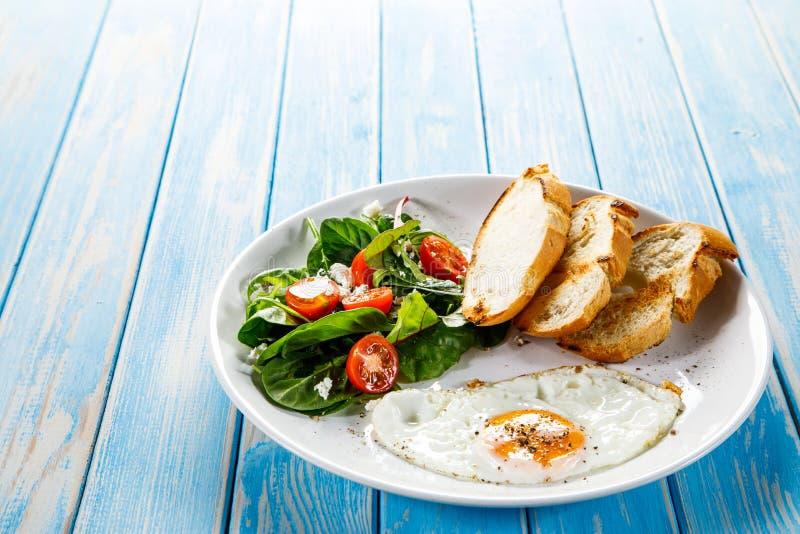 Frukost - stekt ägg, rostade bröd och grönsaksallad fotografering för bildbyråer