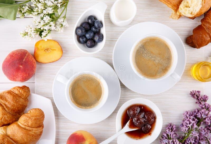 Frukost - två koppar kaffe, giffel, driftstopp, honung och frukter på den vita tabellen royaltyfria foton