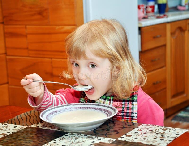frukostbarnet äter porridge royaltyfri bild