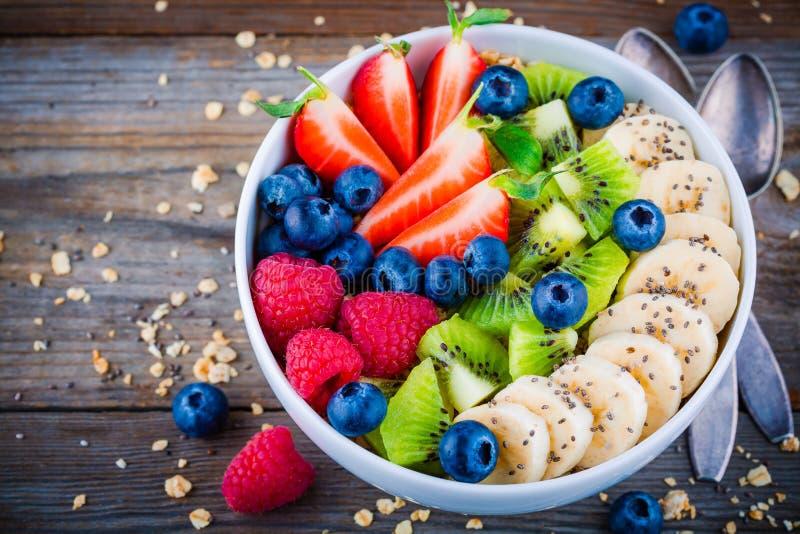 Frukostbunke: granola med banan-, kiwi-, hallon-, jordgubbe-, blåbär- och chiafrö arkivfoto