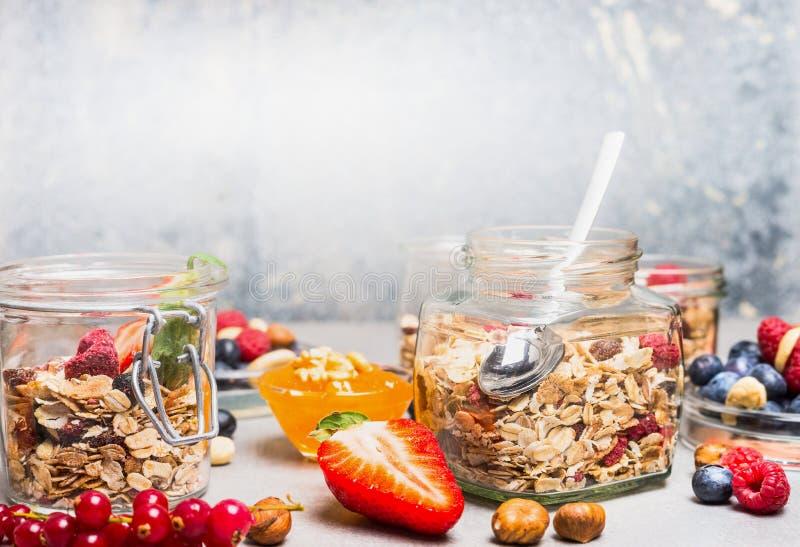 Frukosten i exponeringsglas skorrar med mysli, bär, muttrar och frö på ljus lantlig bakgrund royaltyfria bilder