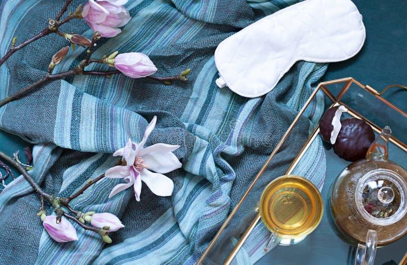 Frukosten i s?ngl?genhet l?gger med magnoliablommor och gr?nt te med marshmallower Terastbegrepp arkivbild