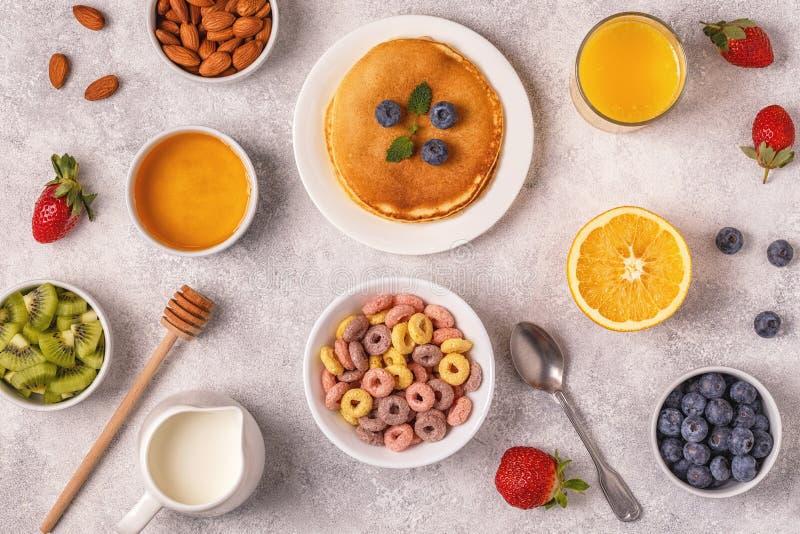 Frukosten med färgrik sädesslag ringer, pannkakor, frukt, mjölkar, juien fotografering för bildbyråer