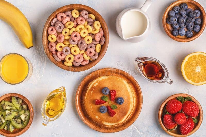 Frukosten med färgrik sädesslag ringer, pannkakor, frukt, mjölkar, juien arkivbild