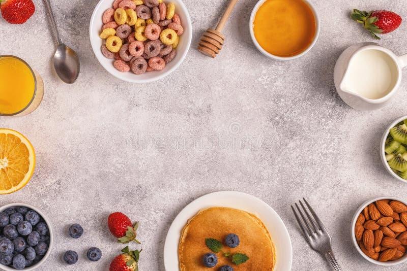 Frukosten med färgrik sädesslag ringer, pannkakor, frukt, mjölkar, juien royaltyfria bilder
