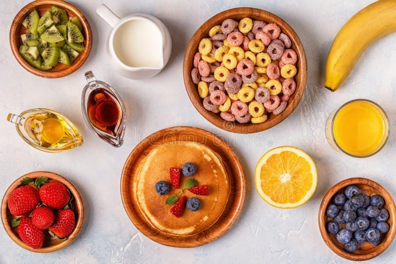 Frukosten med färgrik sädesslag ringer, pannkakor, frukt, mjölkar, juien royaltyfri fotografi