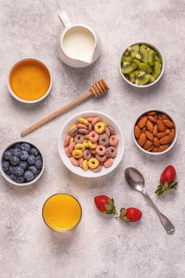 Frukosten med färgrika sädesslagcirklar, frukt, mjölkar, fruktsaft arkivbild