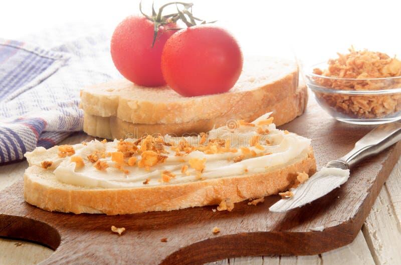 Frukosten med griskött späcker och den frasiga löken på skiva av bröd royaltyfri bild