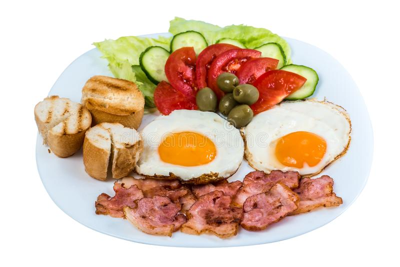 Frukosten stekte ägget som nya grönsaker stekte bacon och oliv på en vit platta royaltyfri foto