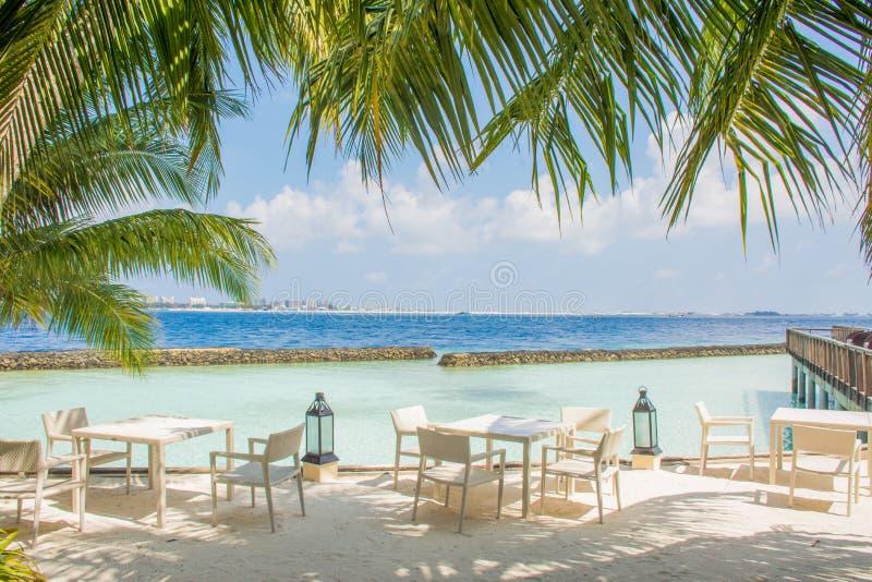 Frukostera aktiveringen med tabeller och stolar på den tropiska stranden arkivfoton