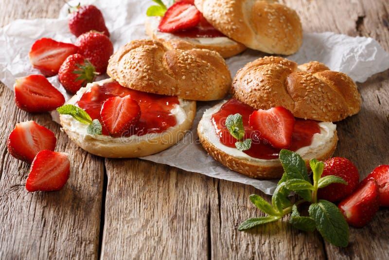 Frukostera bullen med jordgubbedriftstopp, nya bär, kräm och mintkaramellen royaltyfria foton
