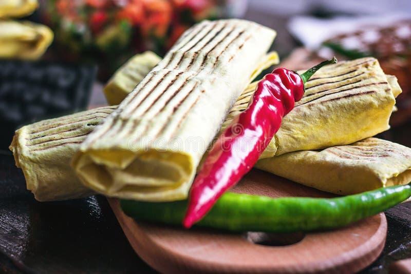 Frukostera den mexikanska snabbmatmatställen för två kryddiga läckra burritos på den wood tabellen för träbrädet som dekoreras me royaltyfria foton