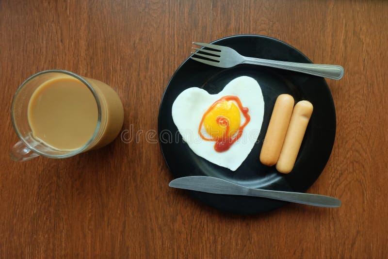 Frukostera, det stekte ägget med korven och kaffe vid fönsterbalkongen i förkylningen Vinter eller regna fotografering för bildbyråer