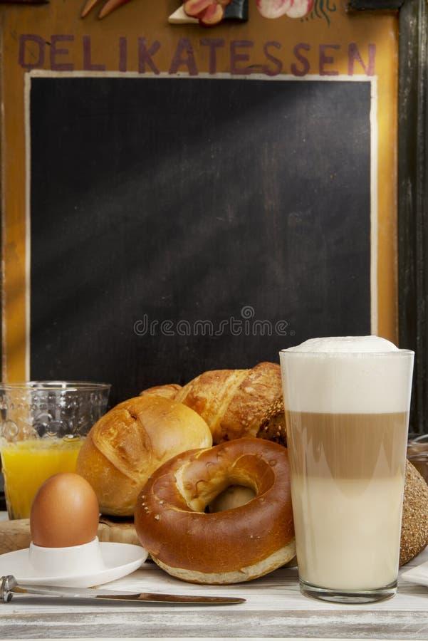 Frukostera i kafét, bröd, bullar, ägget, Lattemacchiatoen, orange fruktsaft royaltyfri fotografi