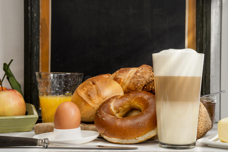 Frukostera i kafét, bröd, bullar, ägget, Lattemacchiatoen, orange fruktsaft arkivbilder