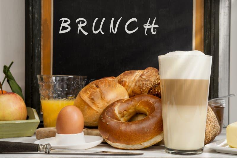 Frukostera i kafét, bröd, bullar, ägget, Lattemacchiatoen, orange fruktsaft arkivfoto