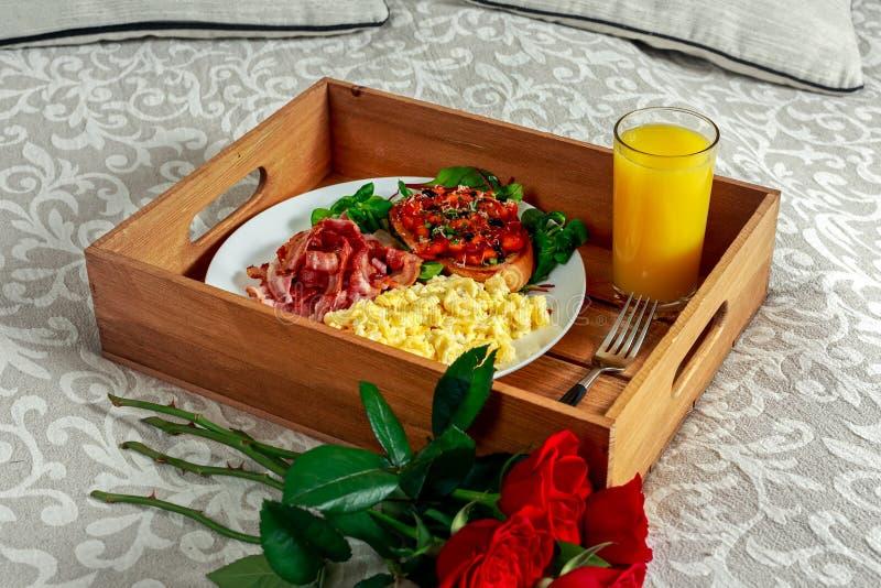 Frukostera i säng på trämagasinet med gruppen av röda rosor Scrumbled ägg, stekt bacon, bönor på rostat bröd och sallad, med arkivfoton