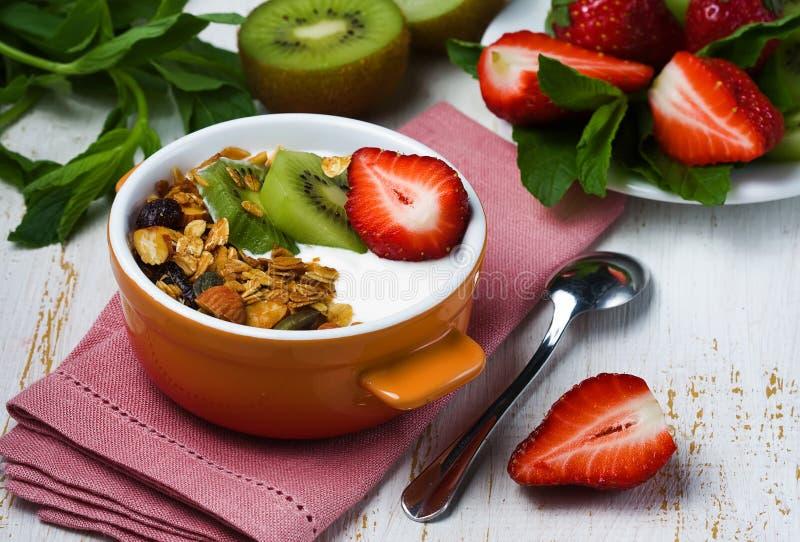 Frukostera med den ny grekisk yoghurt, jordgubbar, kiwin och grano arkivfoto