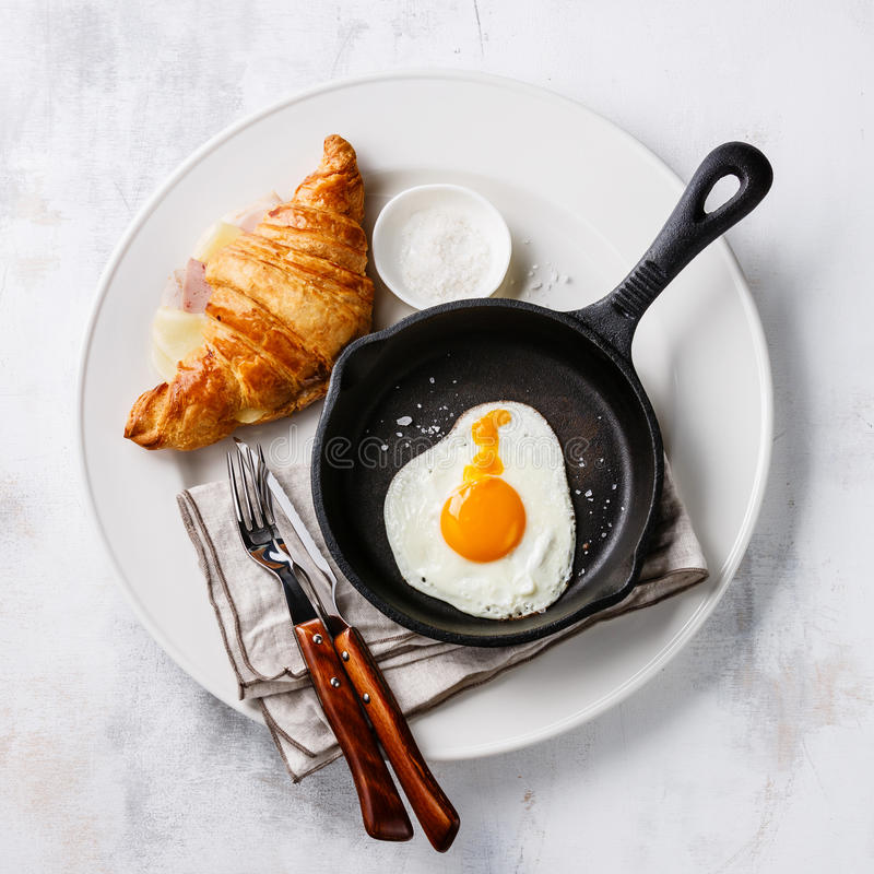 Frukostera med det stekte ägget och gifflet med ost och skinka arkivbilder