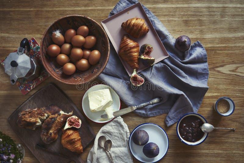 Frukostera med giffel, fikonträd, kaffe på träbräde över lantlig träbakgrund, keramikdisk, varma färger, ovanför sikt royaltyfri bild