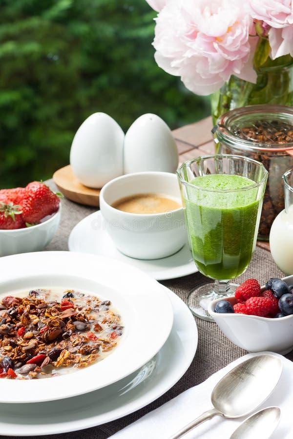 Frukostera med hem- gjord granola, den gröna smoothien och bär royaltyfria bilder
