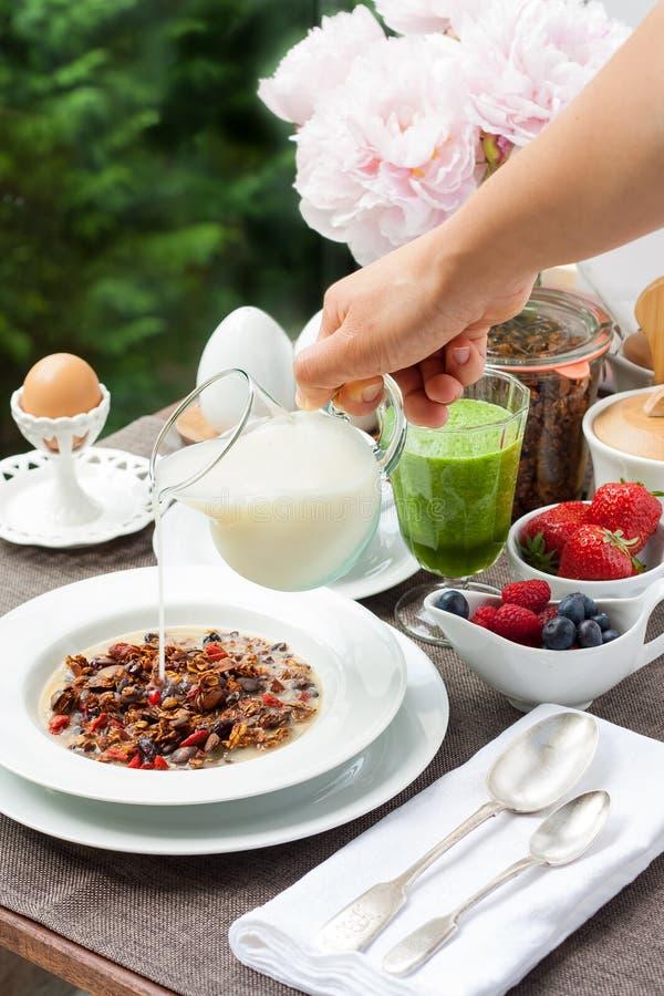 Frukostera med hem- gjord granola, den gröna smoothien och bär royaltyfria foton