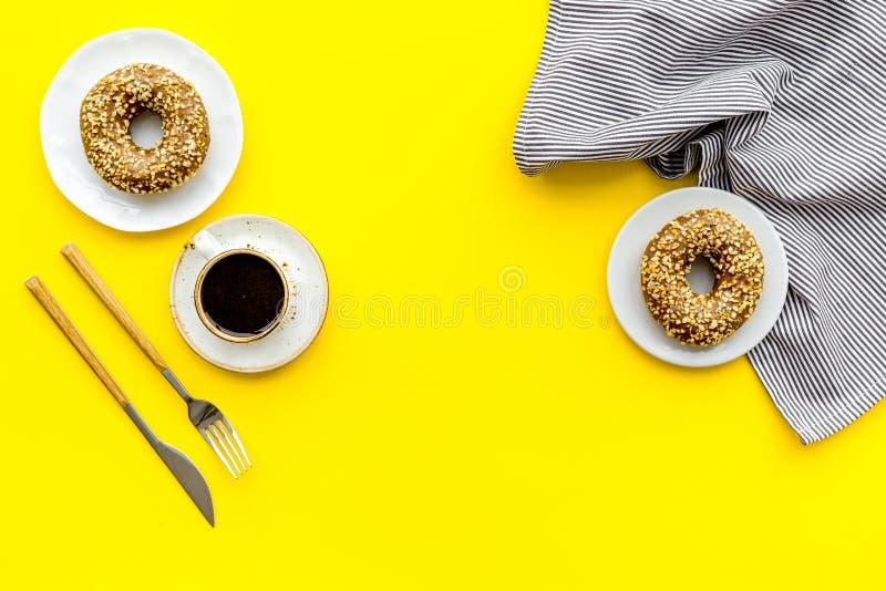 Frukostera med kaffe, donuts och blommor på gul modell för bästa sikt för bakgrund royaltyfri fotografi