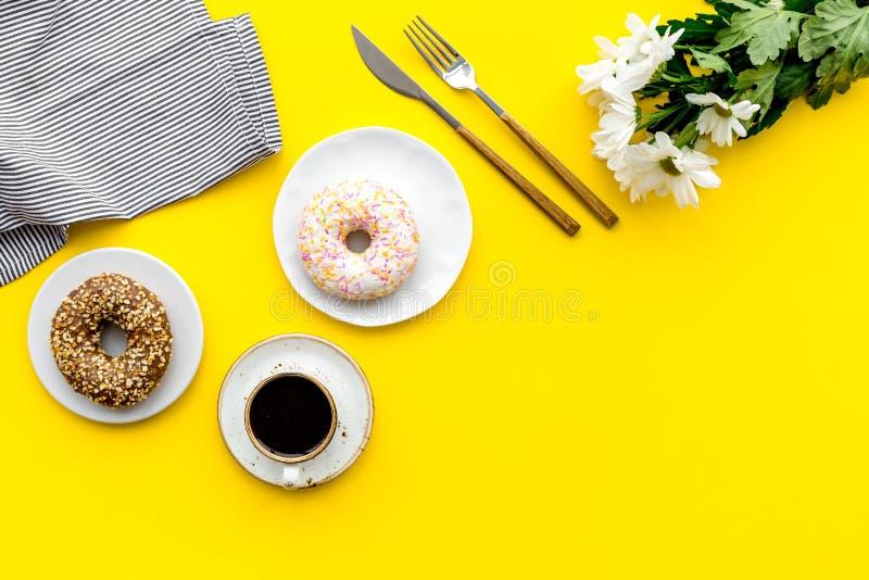 Frukostera med kaffe, donuts och blommor på gul modell för bästa sikt för bakgrund fotografering för bildbyråer